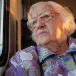elderly woman looking out train window as she travels alone