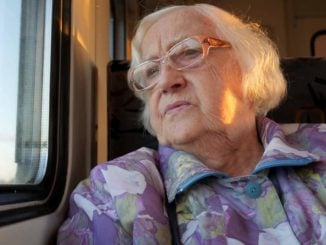 elderly woman looking out train window as she travels alone