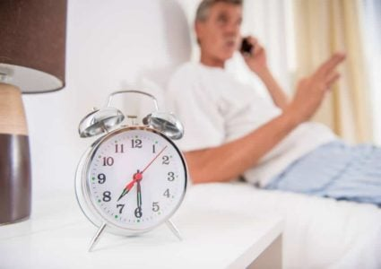 senior man in bed with simple alarm clock in foreground