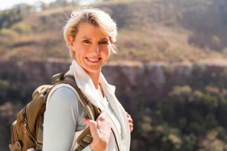 senior woman smiling while wearing a backpack