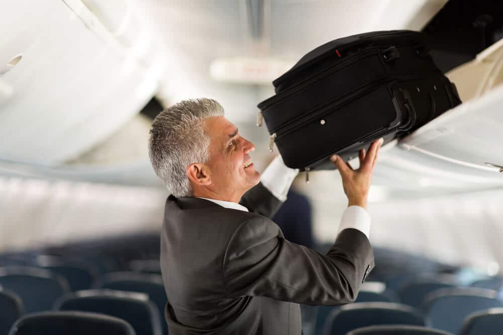 senior man placing carry on luggage in storage bin