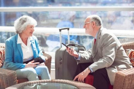 senior couple waiting on a flight with their luggage