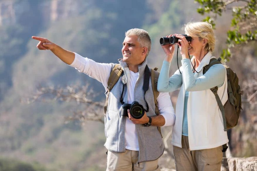 senior couple with binoculars and camera birdwatching in the desert