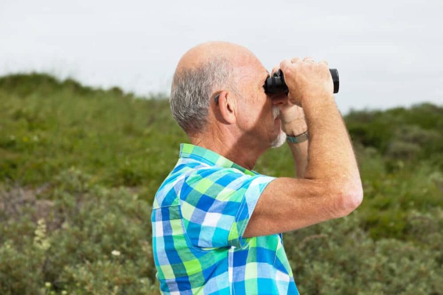 senior man birdwatching with a pair of binoculars