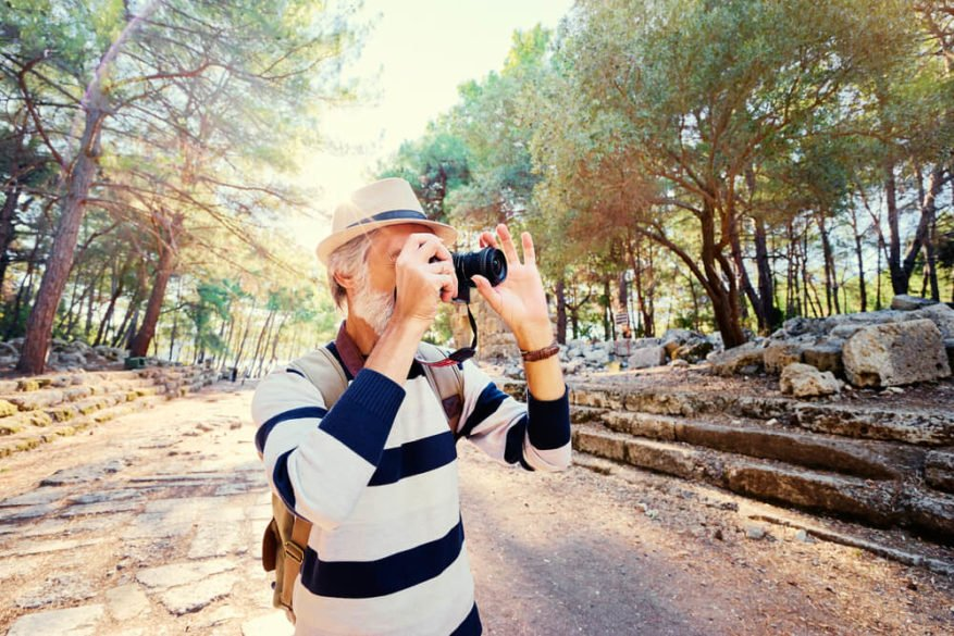 senior man taking photos while on vacation alone