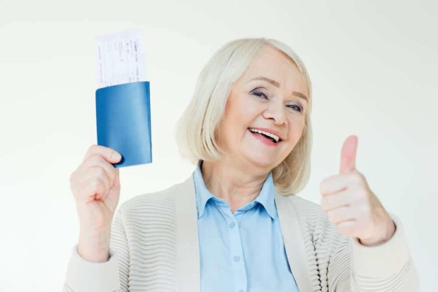 senior woman holding passport and giving a thumbs up