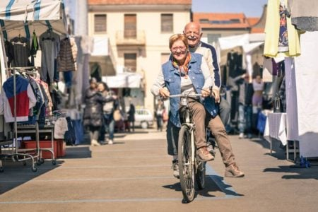 senior couple on a bike enjoying an afternoon at the market