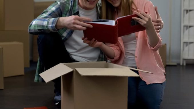 couple taking time to look at a family album while packing boxes to move