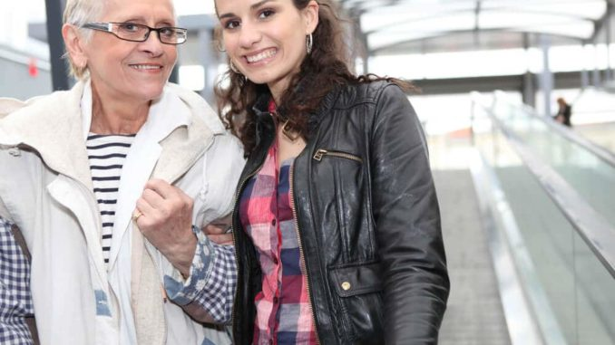 smiling woman traveling with elderly parent