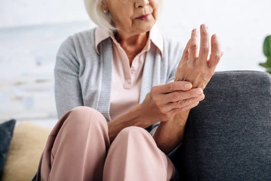 woman rubbing her wrist that hurts due to arthritic pain