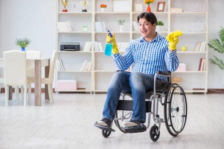 man using supplies to clean his manual wheelchair