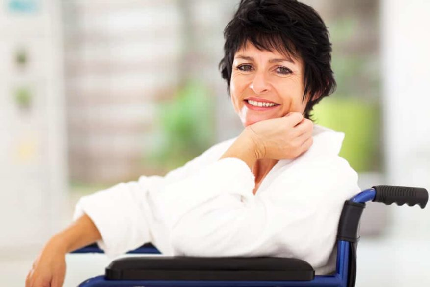 senior woman sitting in wheelchair and smiling at the camera