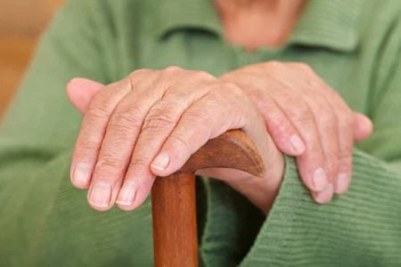 woman showing well manicured fingernails hold a cane