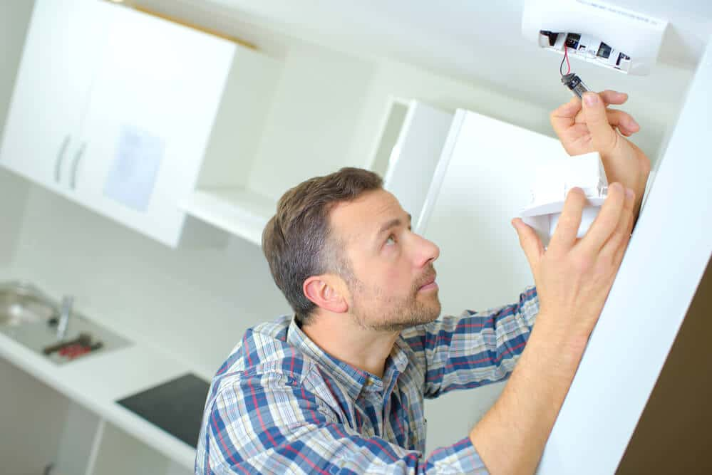 senior man installing smoke detector as part of his fire safety plan