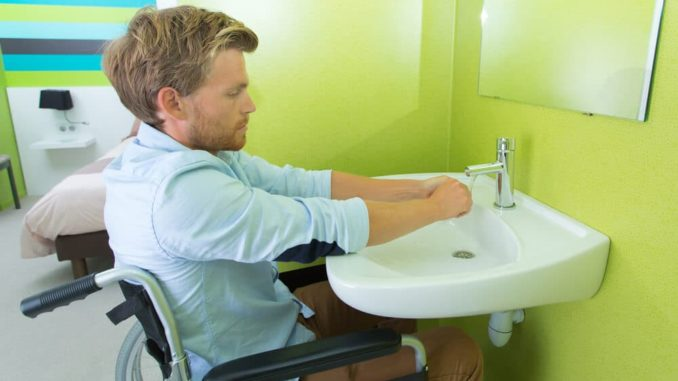 man in wheelchair using the bathroom sink to wash his hands