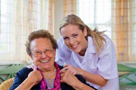 in home care worker helping smiling senior lady