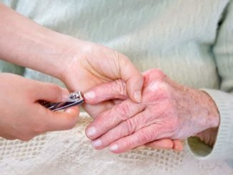woman cutting senior woman's finger nails with nail clippers for arthritic hands