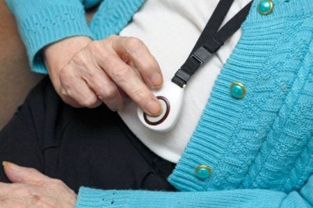 senior woman using one of the best caregiver call buttons to get the help she needs