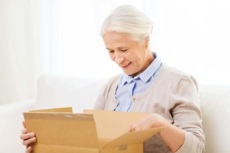 smiling elderly woman opening a delivery she just received
