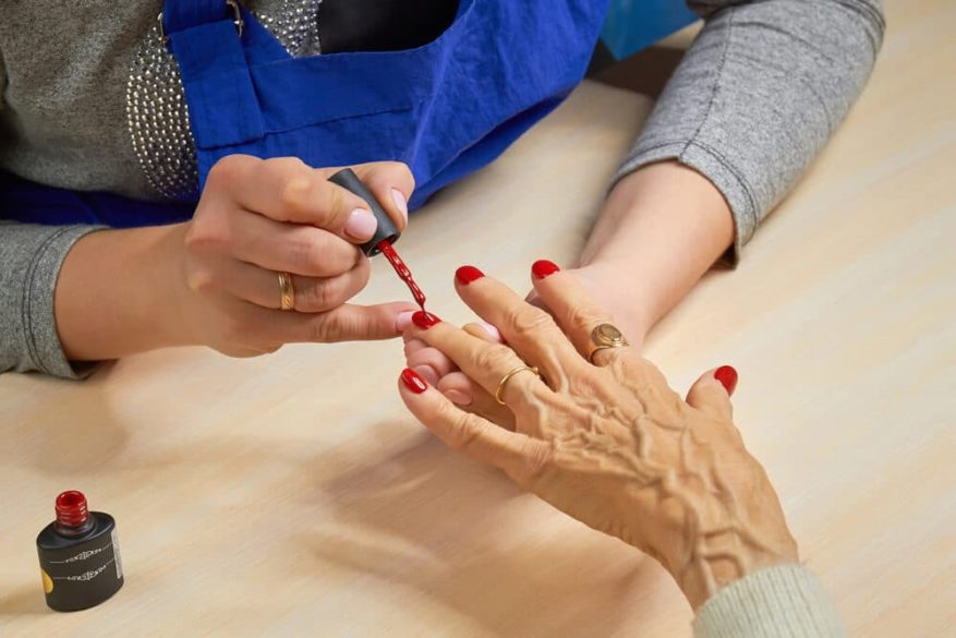senior woman getting her finger nails painted red during a manicure
