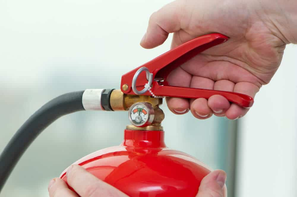 close up of older hand using an easy to use fire extinguisher for elderly people