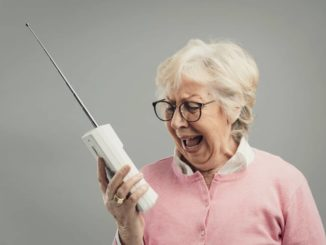 hearing impaired woman yelling at cordless phone because she can't hear