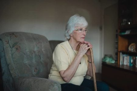 senior woman living alone sitting on couch