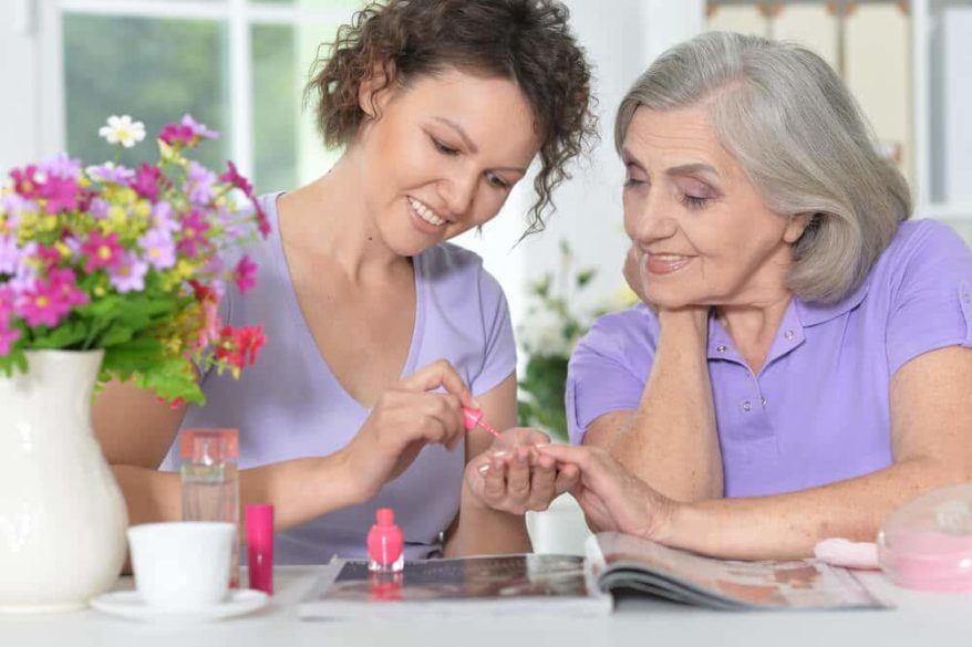 woman giving her senior mother a manicure