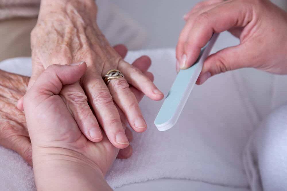 senior woman having nail care done by caregiver