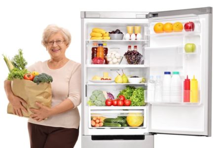 senior woman standing next to a smart refrigerator