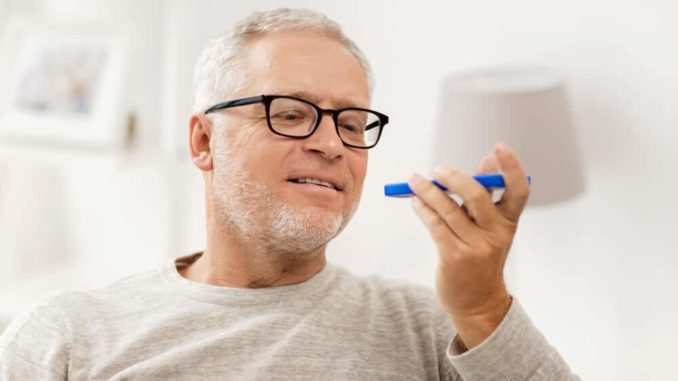 senior man speaking into a simple digital voice recorder