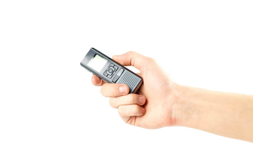 hand holding a digital voice recorder isolated on a white background