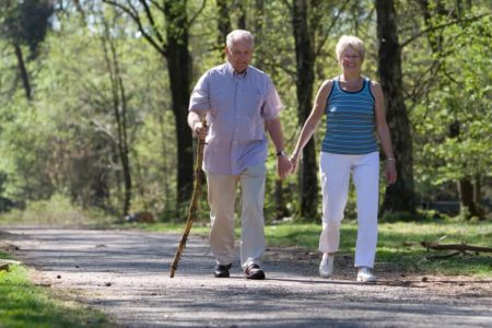 senior couple wearing walking shoes on a walk through the park