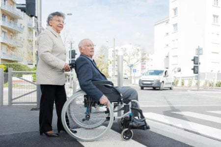 senior couple traveling in a wheelchair friendly city