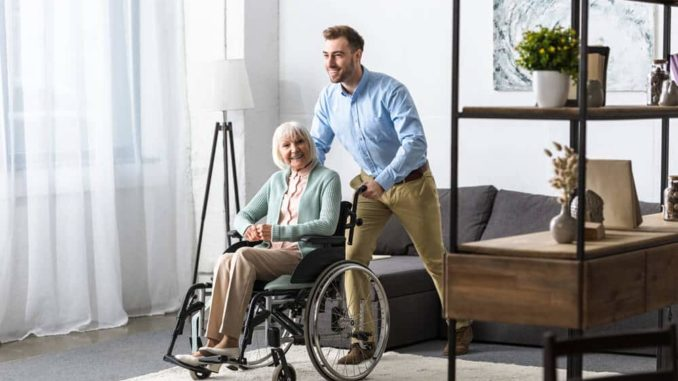 senior woman being pushed through her living room by her caregiver
