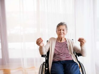 senior woman holding a wheelchair yoga pose
