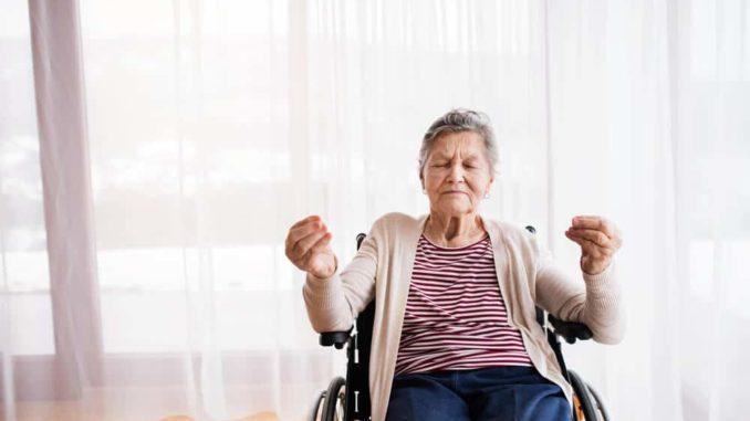 senior woman holding a wheelchair yoga pose