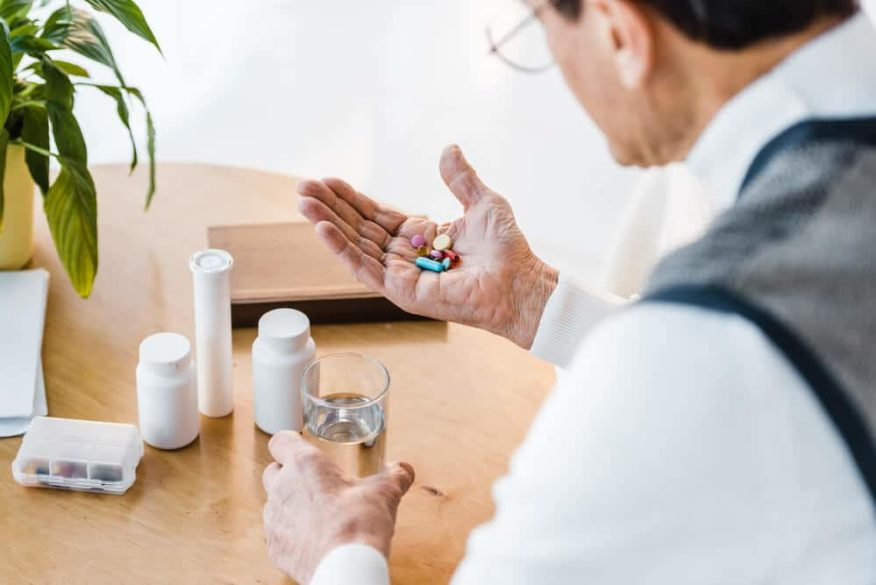 senior man confused by a handful of pills who needs an automatic pill dispenser