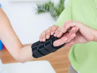 therapist applying wrist brace for sleeping on a patient
