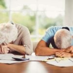 frustrated seniors with head on table and stacks of bills