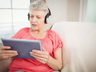 senior woman looking at ipad and wearing headphones for hearing aid wearers