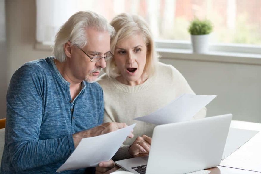 seniors shocked looking at computer after discovering identity theft