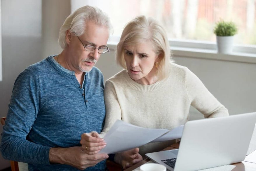 senior couple look over identity theft insurance policy