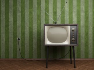 older TV with antenna against the wall