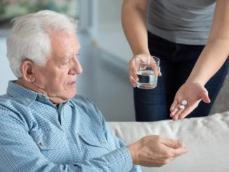 caregiver handling senior man with dementia his pills