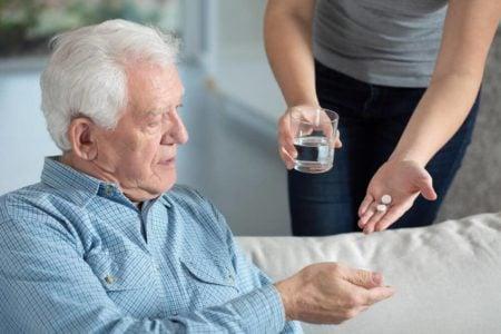 caregiver handling senior man with dementia his pills