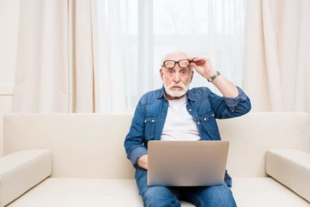 senior man looking at computer trying to decide should seniors buy identity theft insurance