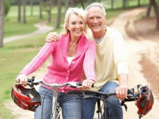 senior couple smiling while riding safe bikes for seniors
