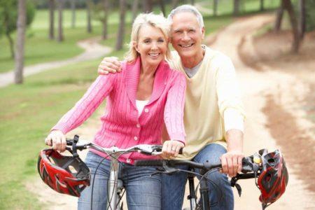 senior couple smiling while riding safe bikes for seniors