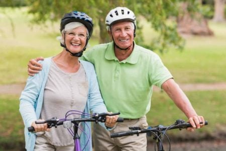 senior couple smiling while wearing bicycle helmets